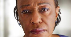 Eine Nahaufnahme einer älteren schwarzen Frau, die traurig schaut Stockbilder