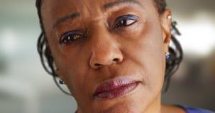 Eine Nahaufnahme einer älteren schwarzen Frau, die weg im Abstand traurig schaut lizenzfreie stockbilder