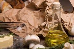 Eine Nahaufnahme einer Flasche Olivenöls umgeben durch Pilze Gemüse eingestellt auf einen Hintergrund des braunen Papiers Lizenzfreies Stockbild