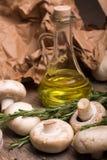 Eine Nahaufnahme einer Flasche Olivenöls umgeben durch Pilze Gemüse eingestellt auf einen Hintergrund des braunen Papiers Stockfotos