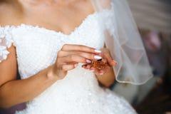 Eine Nahaufnahme einer geernteten Braut in einem Hochzeitskleid hält eine kleine Flasche teures französisches Parfüm in ihren Hän stockbild