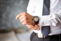 Eine Nahaufnahme eines geernteten Rahmens eines Mannes in einem teuren klassischen Kostüm betrachtet seine Uhr stockfotografie