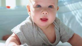 Eine Nahaufnahme eines kleinen Kleinkindes in einer Krippe lachend und versuchend zu kriechen Glückliche Kindheit, kindische Freu stock footage