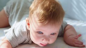 Eine Nahaufnahme eines kleinen Kleinkindes in einer Krippe lachend und versuchend zu kriechen Glückliche Kindheit, kindische Freu stock video