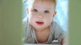 Eine Nahaufnahme eines kleinen Kleinkindes in einer Krippe lachend und versuchend zu kriechen Glückliche Kindheit, kindische Freu stock video footage