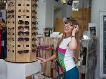 Eine nette Dame, die auf modischen Gläsern auf einem unscharfen Einkaufsspeicherhintergrund versucht Eine Frau in einem Einkaufsz Lizenzfreies Stockbild