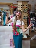Eine nette Dame, die auf modischen Gläsern auf einem unscharfen Einkaufsspeicherhintergrund versucht Eine Frau in einem Einkaufsz Lizenzfreie Stockfotografie