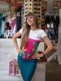 Eine nette Dame, die in den modischen Gläsern auf einem unscharfen Einkaufsspeicherhintergrund aufwirft Eine Frau in einem Einkau Stockbild