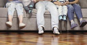 Eine nette Familie sitzt auf der Couch und spielt mit ihren Füßen stock video footage