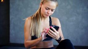 Eine nette Frau, die von einer Sportausbildung graduierte, die durch einen Handy neu geschrieben wurde stock video footage