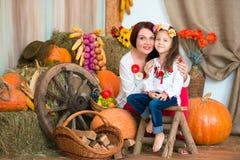Eine nette, lächelnde Mutter und eine Tochter in einem bunten ukrainischen Kranz und in gestickt, sitzt auf Heuschobern Herbstdek lizenzfreie stockfotografie