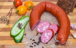 Eine neue geschnittene Hufeisenform der geräucherten Wurst mit Speck und geschnittene grüne Gurke und drei rot und gelbe Tomaten stockbilder