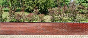 Eine niedrige Hecke von roten Backsteinen umgibt das Yard einer ländlichen Wohnung lizenzfreies stockbild