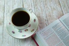 Eine offene heilige Bibel und eine Tasse Tee oder Kaffee Lizenzfreie Stockbilder
