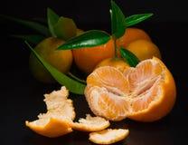 Eine offene Mandarine auf schwarzem Hintergrund Stockfoto