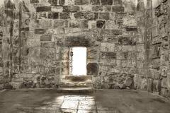 Eine offene Tür, in die helles Sonnenlicht in eine alte Steinwand fällt stockbilder