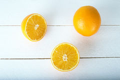 Eine Orange auf einem weißen hölzernen Hintergrund Stockfotografie