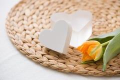 Eine orange Tulpe des neuen Frühlinges und zwei nette Herzsymbole auf dem Strohbrett Hauptromantisches Lizenzfreies Stockfoto