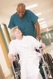 Eine Ordonanz, die eine ältere Frau in einem Rollstuhl drückt lizenzfreie stockbilder
