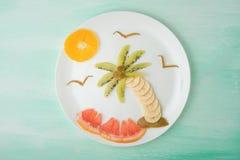 Eine Palme und eine Sonne der Frucht, ein kreatives der Nahrung auf einer weißen Platte Chef gießt Olivenöl über frischem Salat i stockbild
