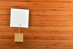 Eine Papieranmerkung mit Halter auf hölzernem Bambushintergrund Lizenzfreies Stockfoto