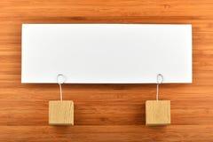 Eine Papieranmerkung mit zwei Haltern lokalisiert auf hölzernem Hintergrund Stockbild