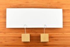 Eine Papieranmerkung mit zwei Haltern lokalisiert auf hölzernem Hintergrund Stockbilder