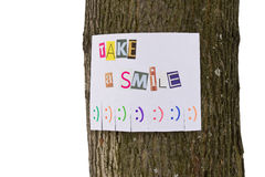 Eine Papieranzeige mit der Phrase: Nehmen Sie ein Lächeln und mit Lächelnzeichen Stockbilder