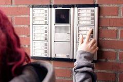 Eine Person bedrängt einen Knopf auf einer Wechselsprechanlage lizenzfreies stockfoto