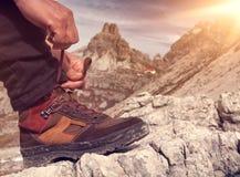 Eine Person bindet das Wandern von Schuhen in der Gebirgsnahaufnahme lizenzfreie stockbilder