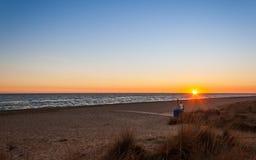 Eine Person, die den Sonnenuntergang auf dem Strand schaut Lizenzfreies Stockbild