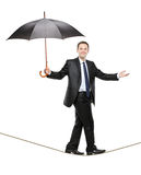Eine Person, die einen Regenschirm anhält und auf ein Seil geht Lizenzfreie Stockbilder