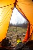 Eine Person, die im Frühjahr in einem orange Zelt, Lager in der Bank des Flusses sitzt Füße selfie des Reisenden Entspannter, bun Lizenzfreies Stockfoto