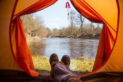 Eine Person, die im Frühjahr in einem orange Zelt, Lager in der Bank des Flusses sitzt Füße selfie des Reisenden Entspannter, bun Stockbilder