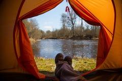 Eine Person, die im Frühjahr in einem orange Zelt, Lager in der Bank des Flusses sitzt Füße selfie des Reisenden Entspannter, bun Lizenzfreie Stockfotografie