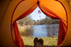 Eine Person, die im Frühjahr in einem orange Zelt, Lager in der Bank des Flusses sitzt Füße selfie des Reisenden Entspannter, bun Lizenzfreie Stockbilder