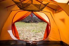 Eine Person, die im Frühjahr in einem orange Zelt, Lager in der Bank des Flusses sitzt Füße selfie des Reisenden Entspannter, bun Stockfotografie