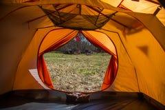 Eine Person, die im Frühjahr in einem orange Zelt, Lager in der Bank des Flusses sitzt Füße selfie des Reisenden Entspannter, bun Stockbild