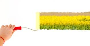 Eine Person, die eine Landschaft mit gelben Blumen auf einer weißen Wand mit einer Rollenbürste malt Stockbilder