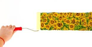 Eine Person, die eine Landschaft mit Sonnenblumen auf einer weißen Wand mit einer Rollenbürste malt Lizenzfreies Stockfoto