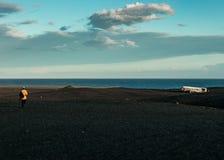 Eine Person, die in Richtung zur Küste des Meeres mit verlassenem zerschmettertem Flugzeug auf der Seite geht lizenzfreies stockbild