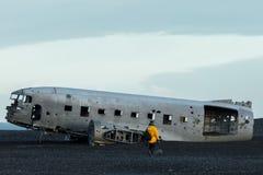 Eine Person in einem gelben Regenmantel, der einem alten zerschmetterten Flugzeug auf einem Gebiet sich nähert lizenzfreies stockfoto