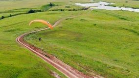 Eine Person geht unten während Fliegen der Parawing Gleitschirmfliegen stock video footage