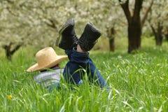 Eine Person im Hut, der sich auf grünem Feld hinlegt Lizenzfreies Stockfoto