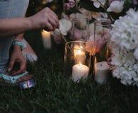 Eine Person legt Feuer auf eine Kerze in einem Glas Ein Dekorateur verziert eine Halle in der Dunkelheit stockbild