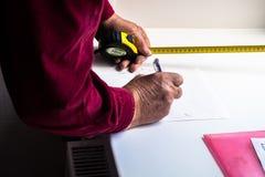 Eine Person macht Berechnungen auf Papier Stockbild