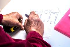 Eine Person macht Berechnungen auf Papier Lizenzfreie Stockfotos