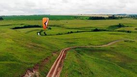 Eine Person mit dem Gleitschirm fliegt in die Luft Gleitschirm über der Wiese stock footage