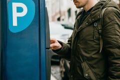 Eine Person oder ein Tourist zahlt für Autoparken in einer Straßenparkmaschine lizenzfreies stockfoto