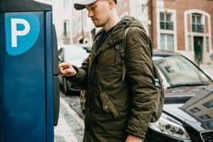Eine Person oder ein Tourist zahlt für Autoparken in einer Straßenparkmaschine lizenzfreie stockfotografie